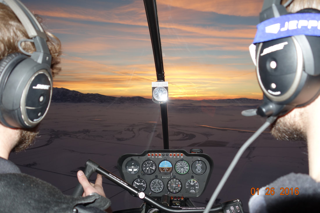 A helicopter certified flight instructor with a student navigating western mountains during the winter.